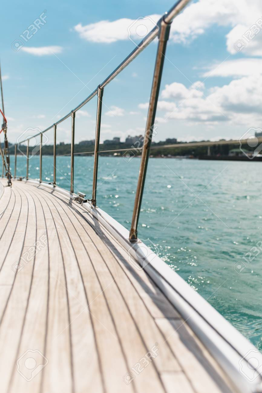 Sailing boat deck on a white yacht with teak wooden deck and..