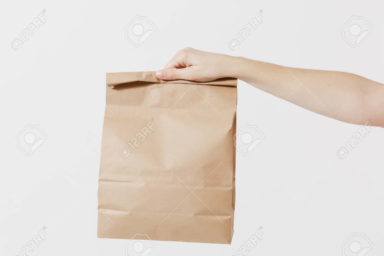 Close up female holds in hand brown clear empty blank craft paper bag for takeaway isolated on white background. Packaging template mockup. Delivery service concept. Copy space. Advertising area - 104187442