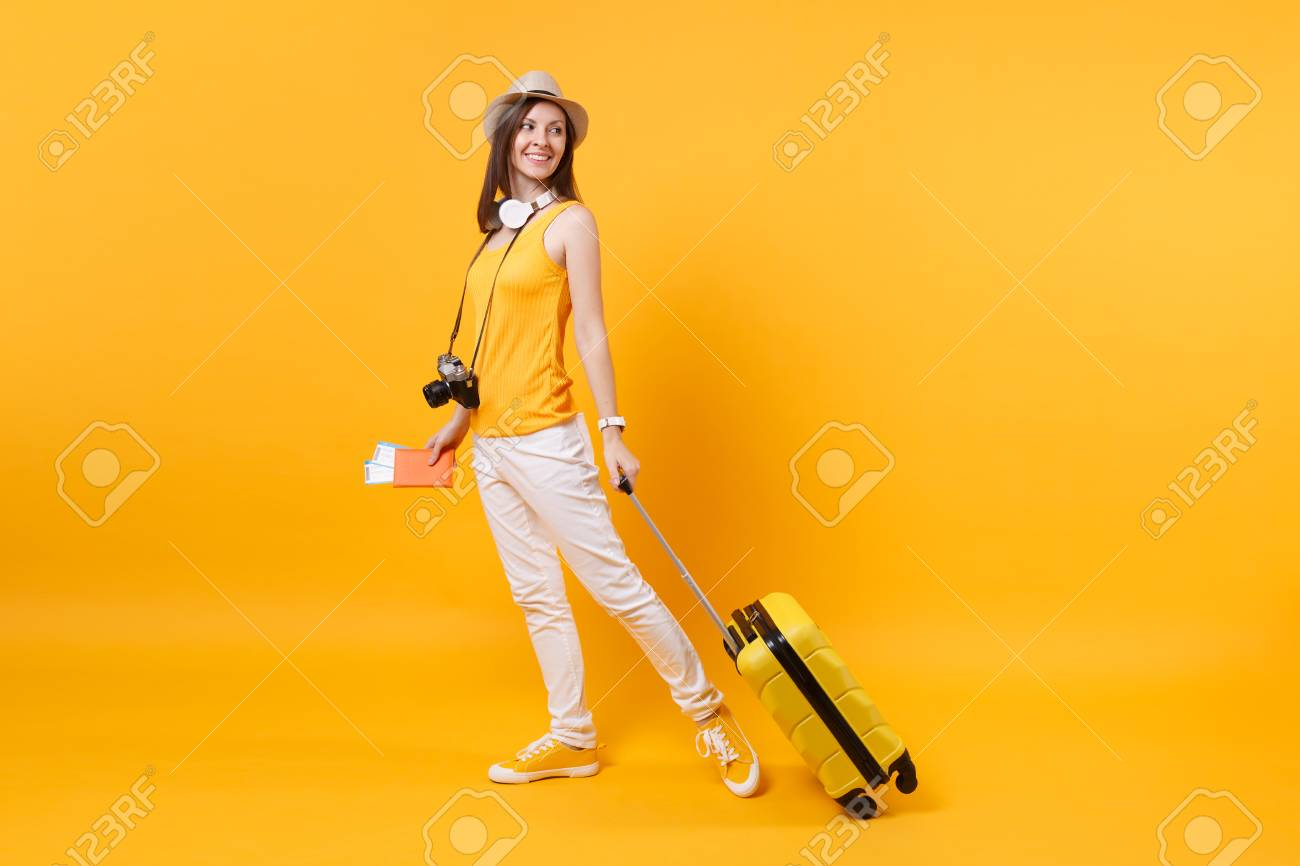 Traveler tourist woman in summer casual clothes, hat with headphones on neck isolated on yellow orange background. Passenger traveling abroad to travel on weekends getaway. Air flight journey concept - 107556319