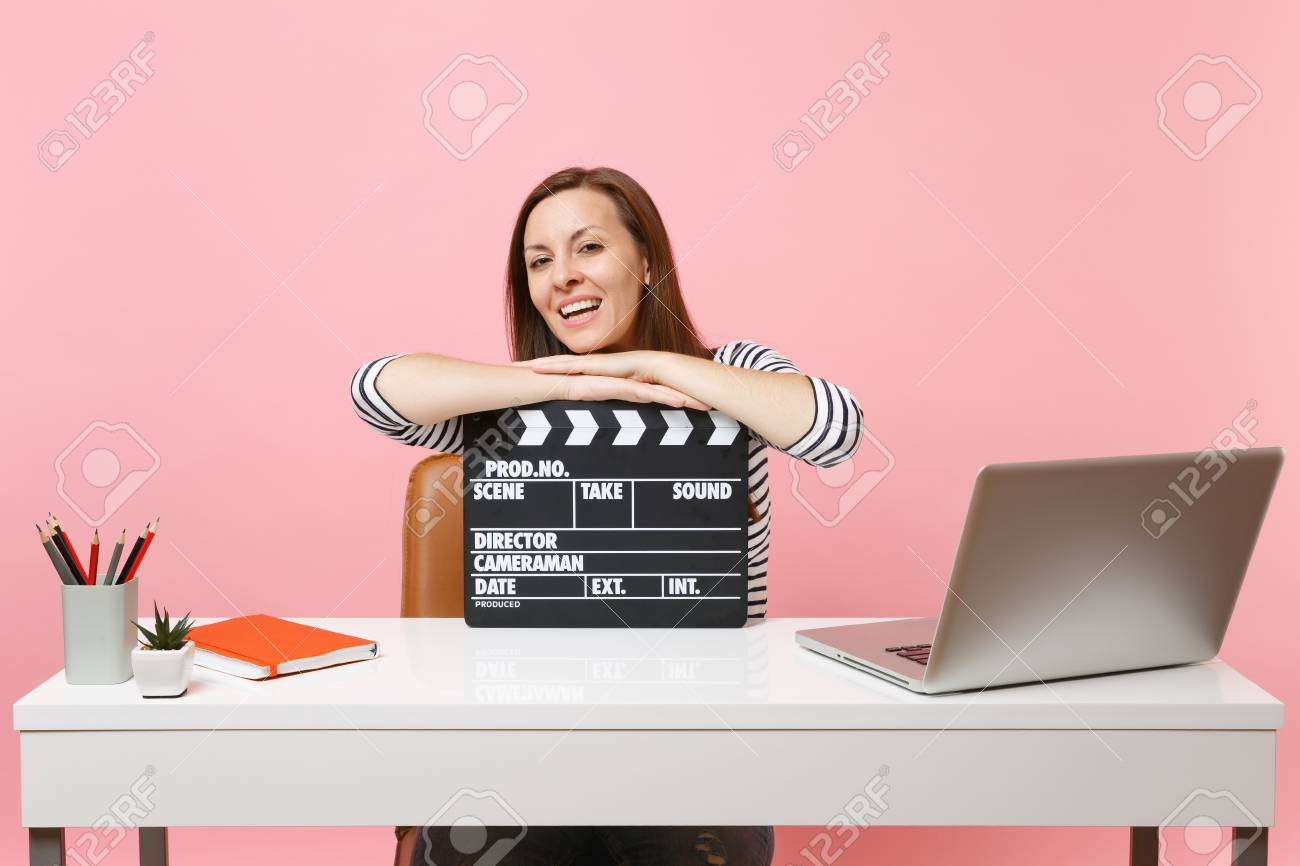 Young laughing woman leaning on classic black film making clapperboard