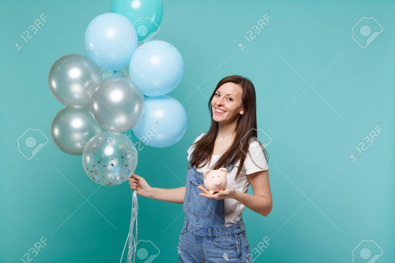 Portrait of smiling young woman in denim clothes holding piggy money bank celebrating with colorful air balloons isolated on blue turquoise background. Birthday holiday party, people emotions concept - 116188778