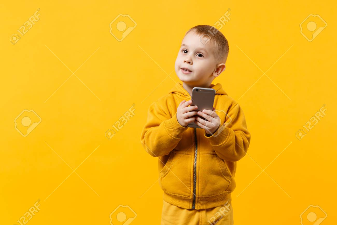 Little cool kid boy 3-4 years old in yellow clothes talking on