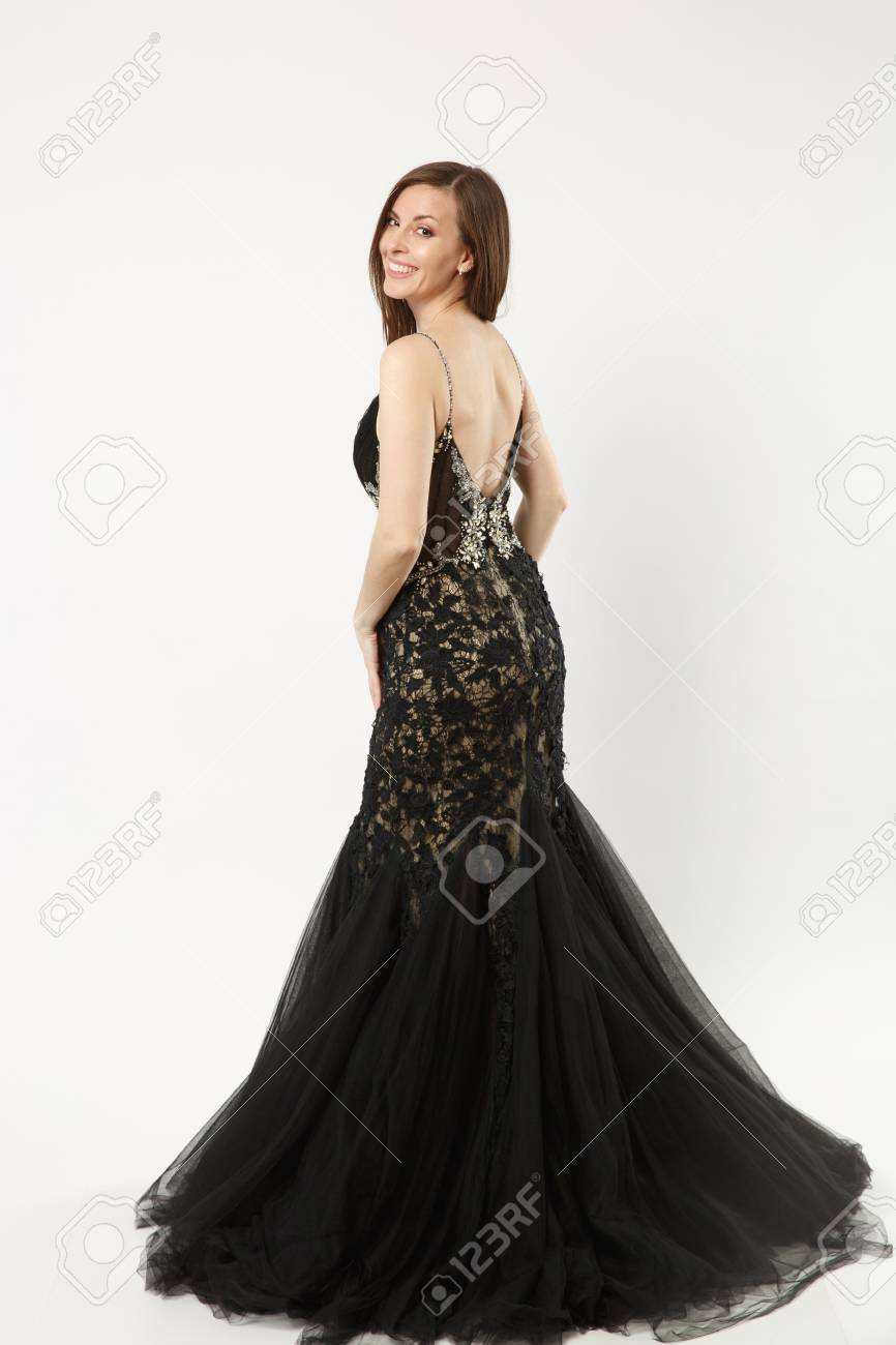 9094d6b8b5a Full length photo of fashion model woman wearing elegant evening dress black  gown posing isolated on white wall background studio portrait.