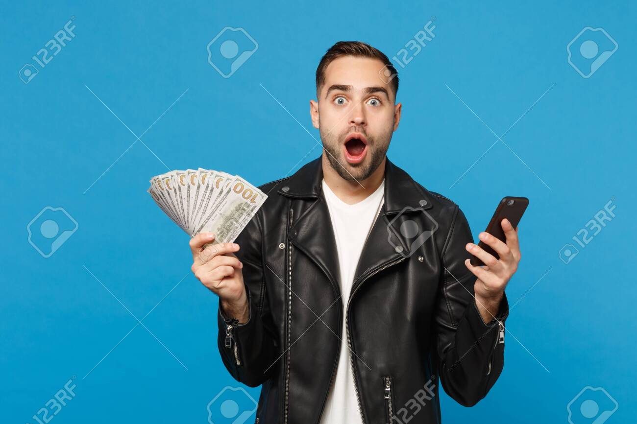 Young man in black leather jacket white t-shirt holding fan of cash money in dollar banknotes, cellphone isolated on blue wall background studio portrait. People lifestyle concept. Mock up copy space - 122091208