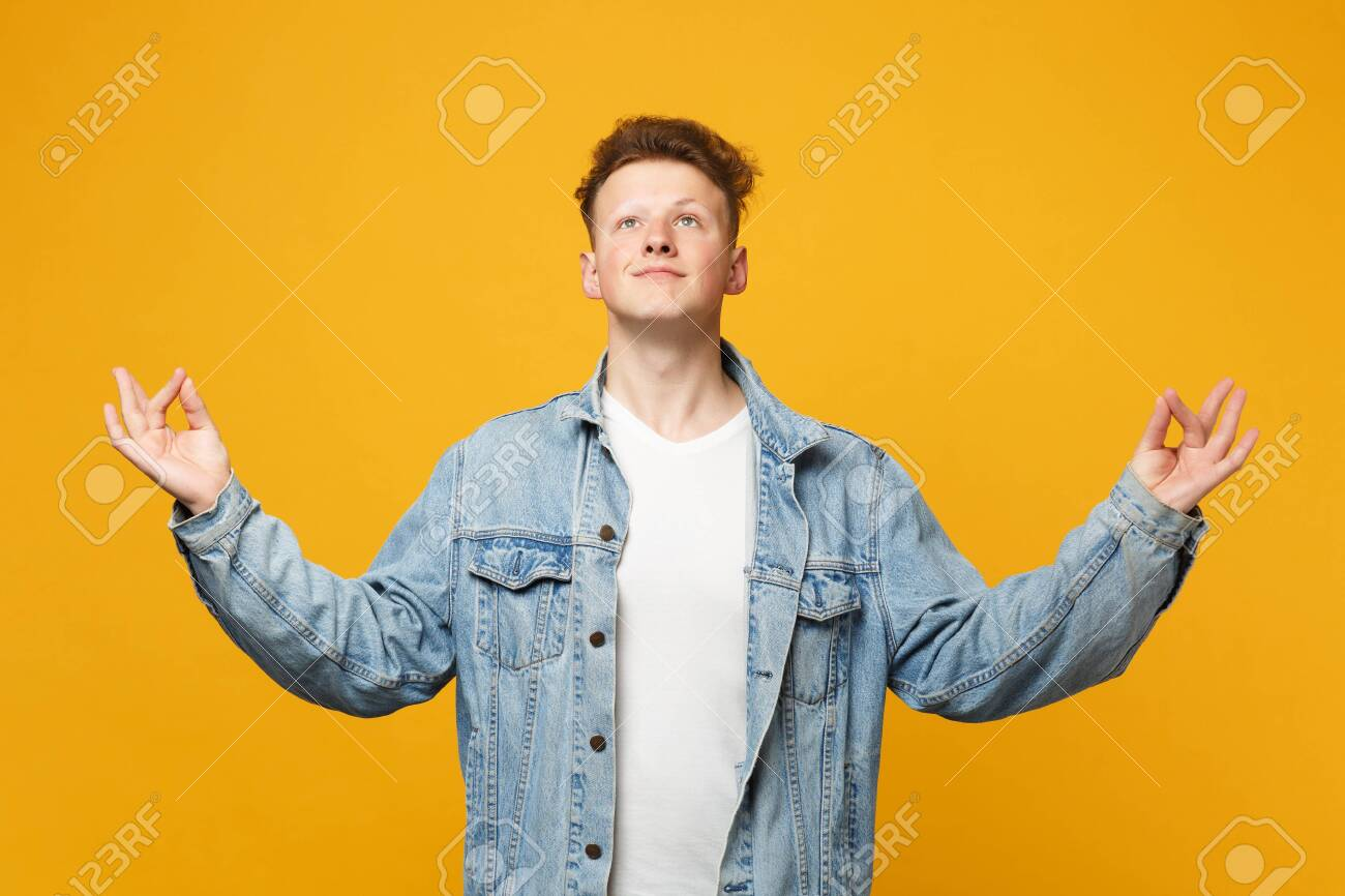 Handome young man in denim casual clothes looking up hold hands in yoga gesture relaxing meditating isolated on yellow orange background. People sincere emotions lifestyle concept. Mock up copy space - 124534313