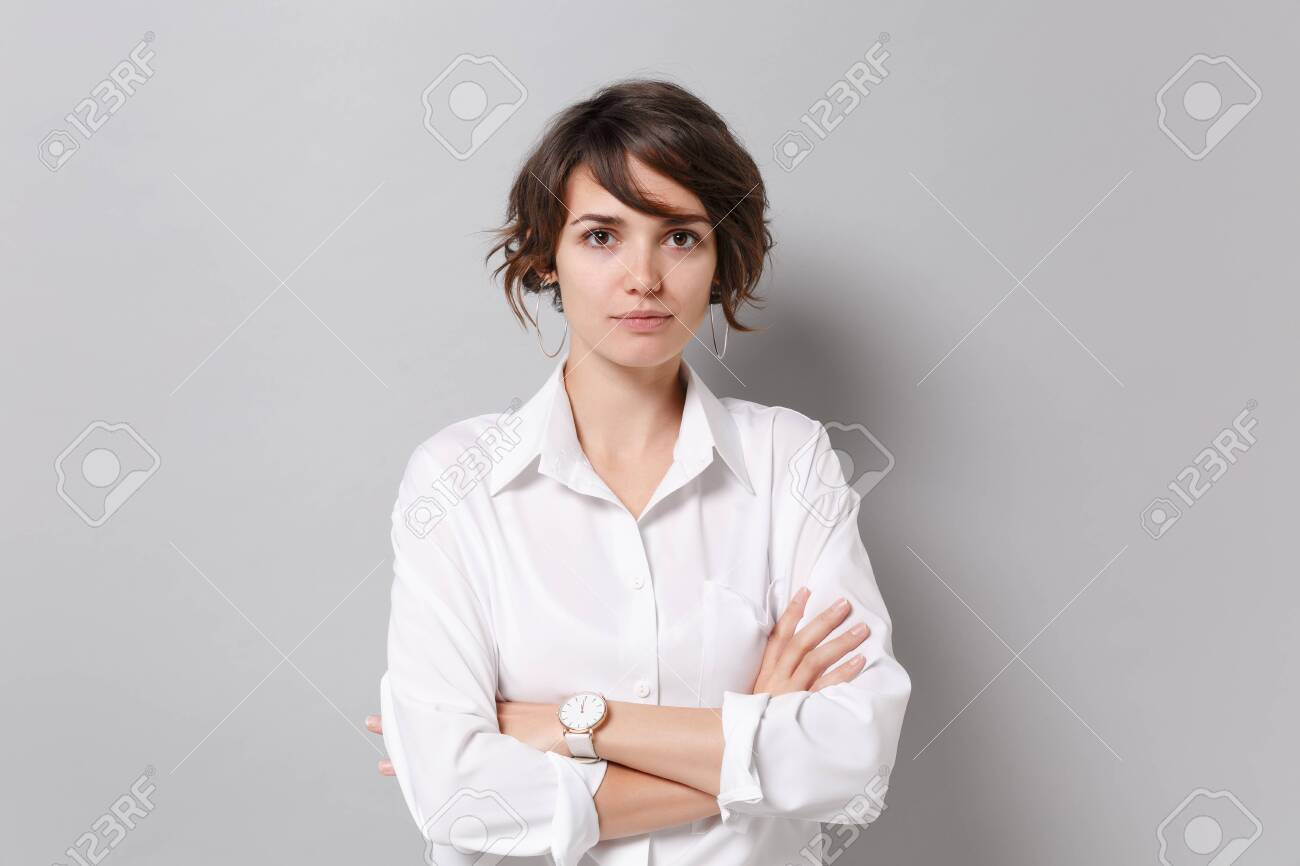 Beautiful young business woman in white shirt posing isolated on grey background studio portrait. Achievement career wealth business concept. Mock up copy space. Holding hands crossed, looking camera. - 151806321