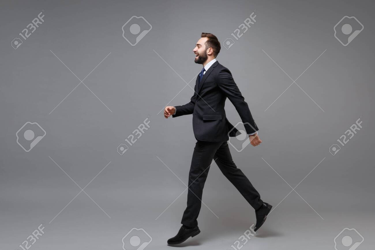Side view of laughing young business man in classic suit shirt tie posing isolated on grey background. Achievement career wealth business concept. Mock up copy space. Running, jumping, looking aside. - 152006946