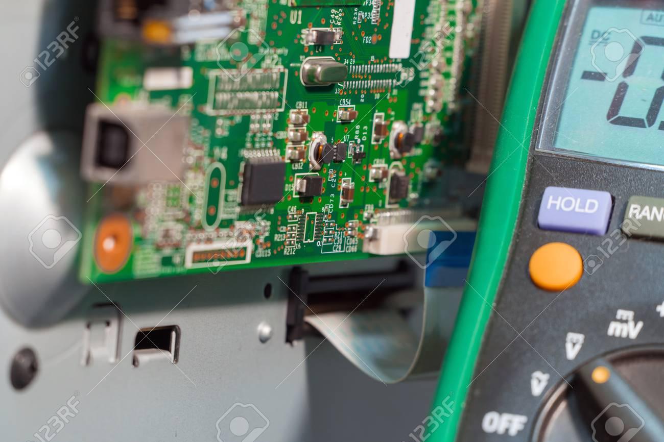 Printer motherboard and multimeter  Repair of office equipment
