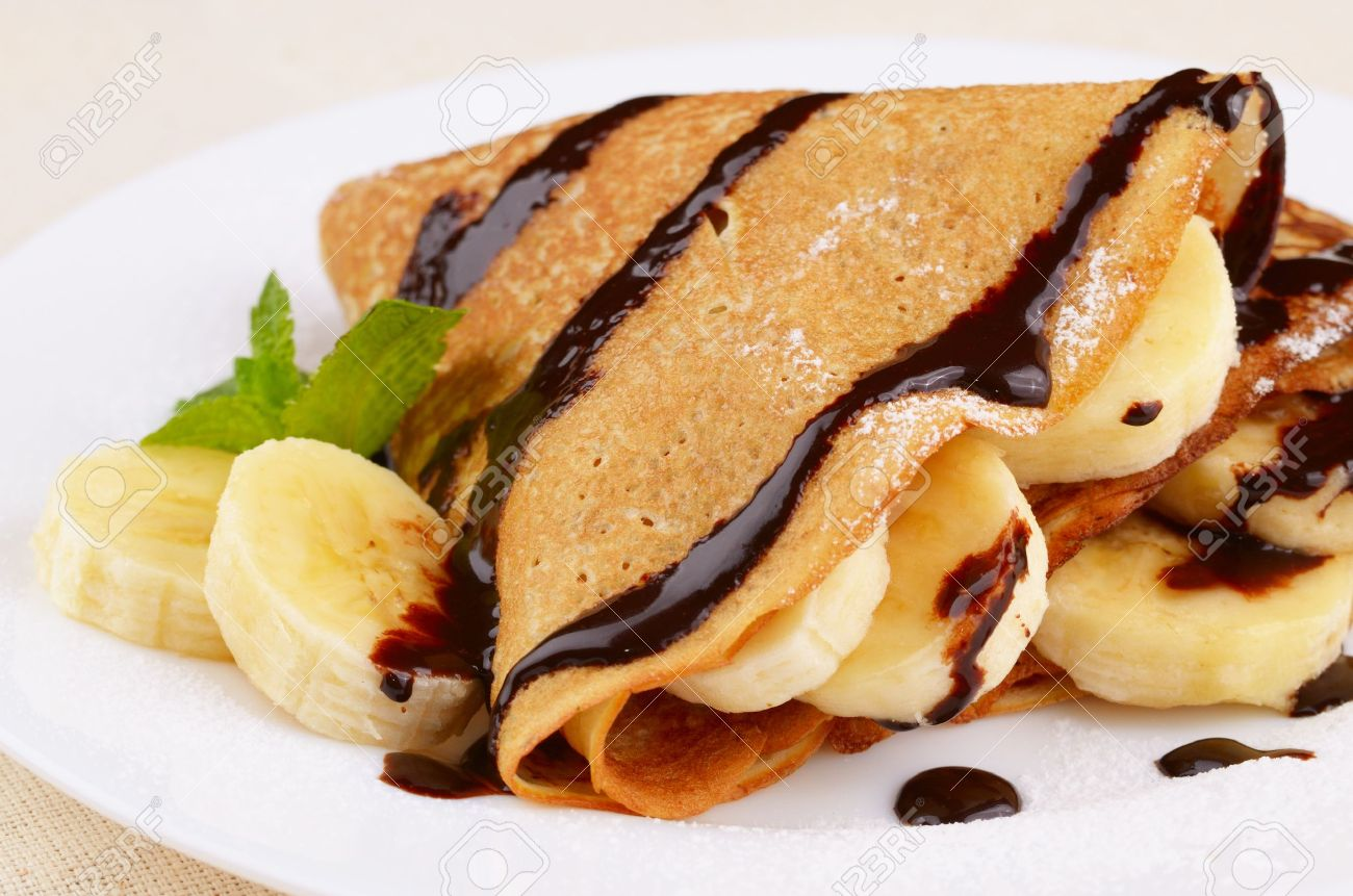 French style crepes with banana, chocolate sauce and sugar powder Stock Photo - 11770860