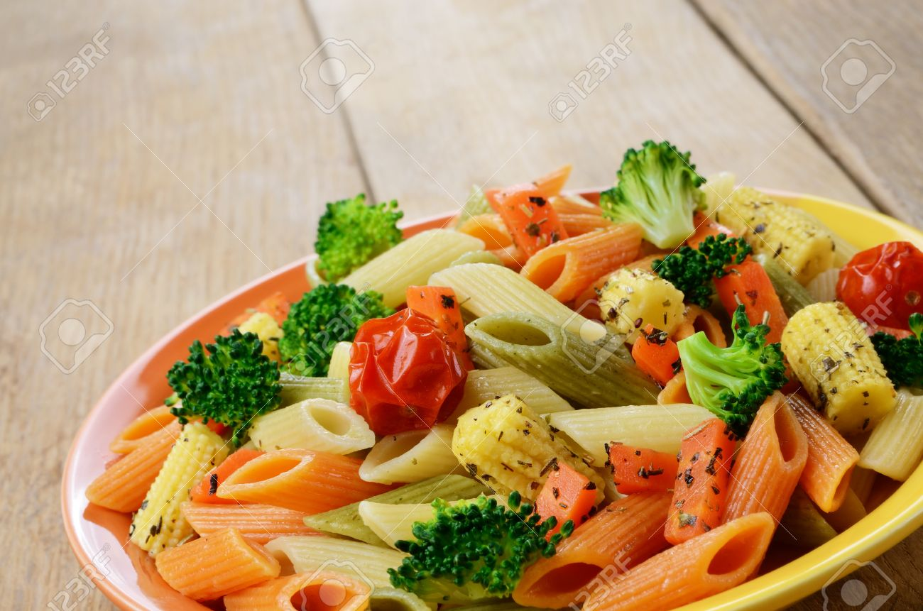 Pasta Penne Salad With Broccoli Carrot Corn And Tomatoes On The Wooden Table