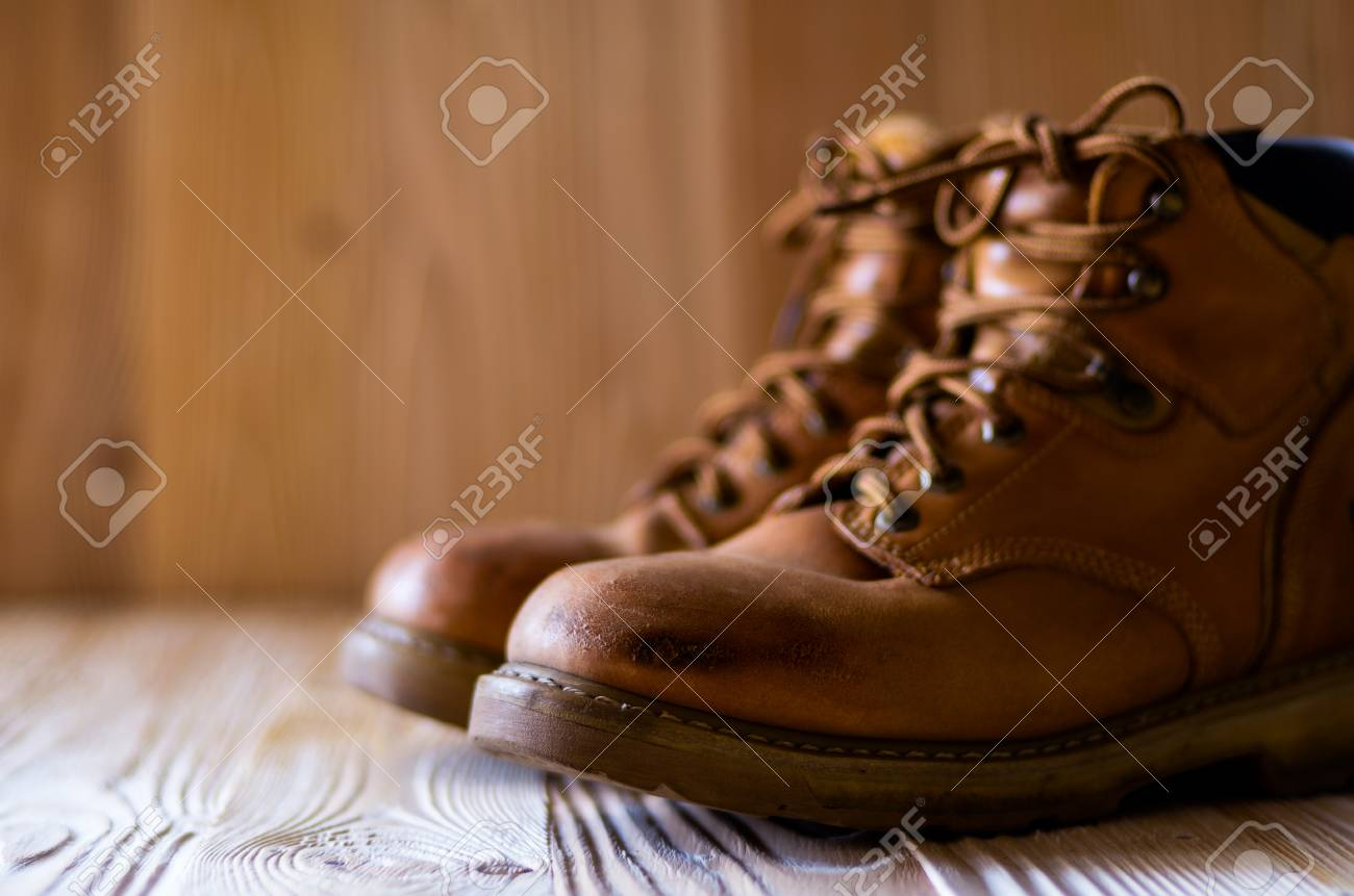 Yellow leather used work boots on wooden closeup. Place for..