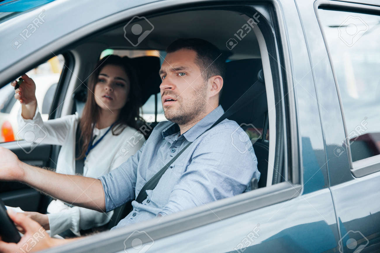 Female instructor showing something by his hand on the road and giving advice. Male student listening to his teacher, looking ahead with concentration and holding wheel. Driving school concept. - 157808617