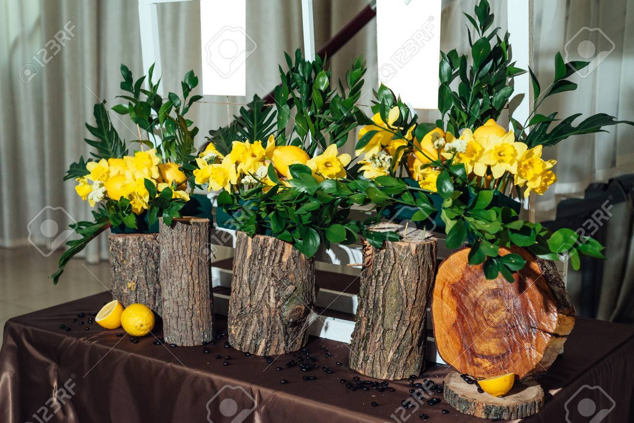 Wedding flower arrangements of yellow daffodils greenery and stock photo wedding flower arrangements of yellow daffodils greenery and lemons on stumps under seating plan for wedding reception guests list close up mightylinksfo