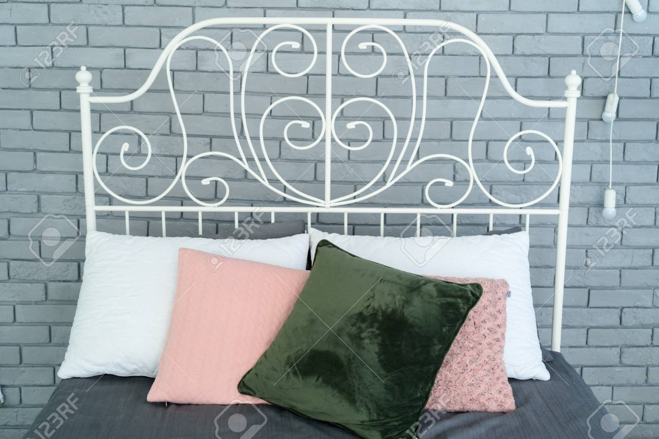 2a8f3dcc130c Colored pillows on white metal frame bed with decorative metal headboard  near grey brick wall Stock