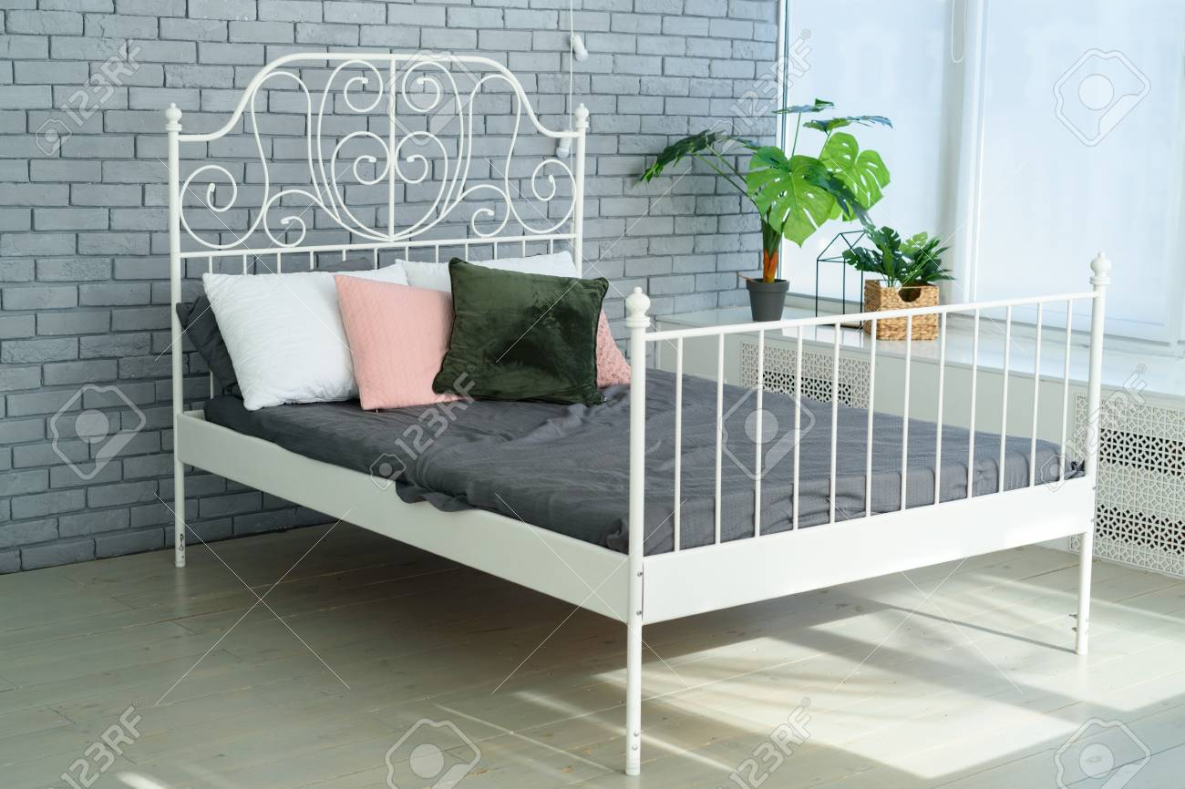 a9007f18ea3d Large white metal frame bed with decorative metal headboard and white, pink  and green pillows