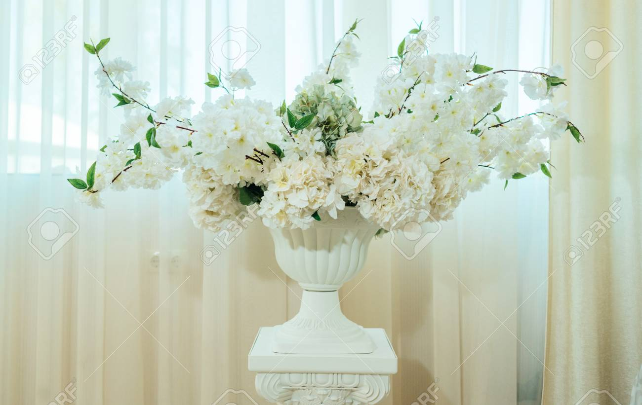 White flowers in a white antique vase near the window stock photo stock photo white flowers in a white antique vase near the window mightylinksfo