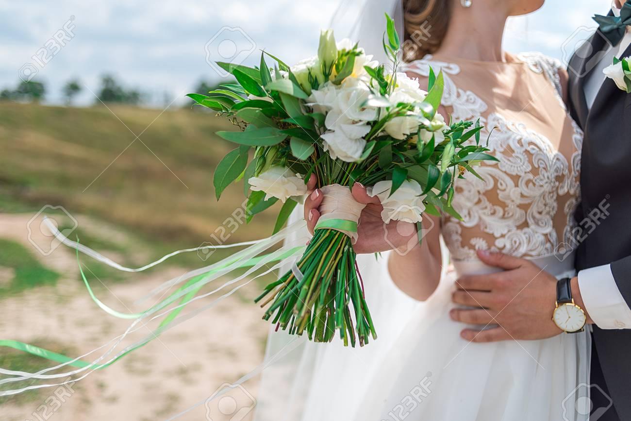 Beautiful bridal bouquet of white fresh flowers and greenery stock beautiful bridal bouquet of white fresh flowers and greenery with ribbons in brides hand selective izmirmasajfo