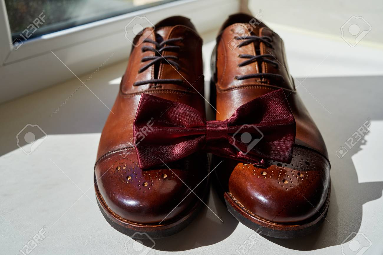 a5f921f18673 Close up of burgundy man bowtie on brown leather man shoes. Modern man  accessories.