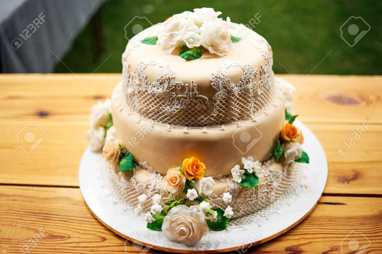 Elegant Beige Multi Level Wedding Or Birthday Cake Decorated With Flowers And Lace On Wooden Table