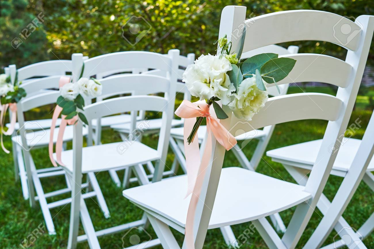 White Fresh Flowers With Pink Ribbon On Wedding Chair On Each