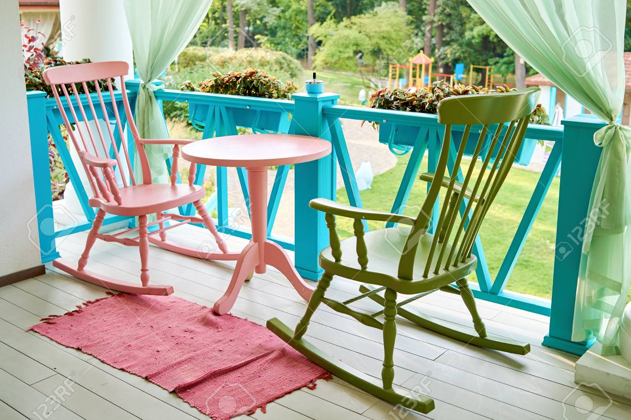 Picture of: Pink And Green Wooden Rocking Chairs And Table On Porch Or Balcony Stock Photo Picture And Royalty Free Image Image 103839404