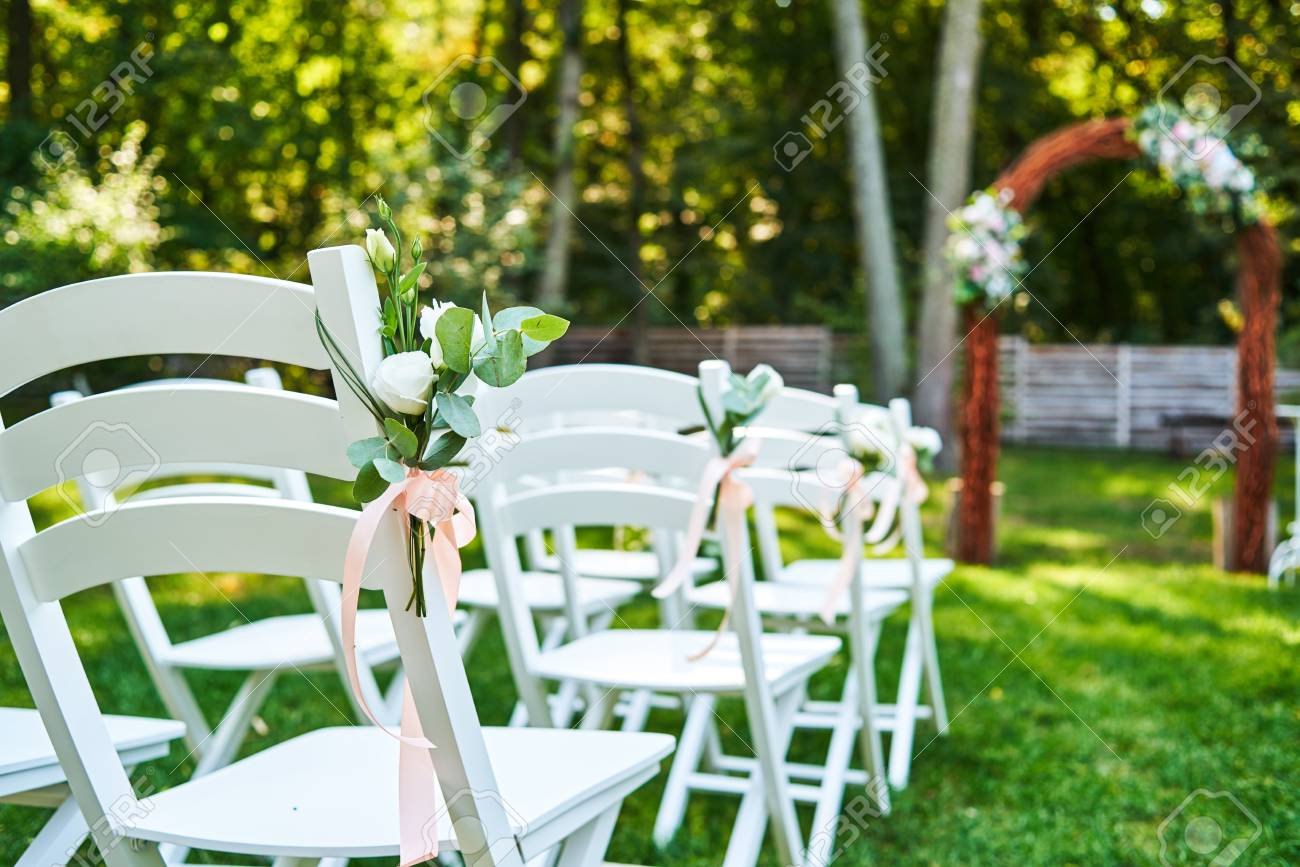 White fresh flowers with pink ribbon on wedding chair on each stock photo white fresh flowers with pink ribbon on wedding chair on each side of archway outroods copy space wooden chairs for guests on green grass in mightylinksfo