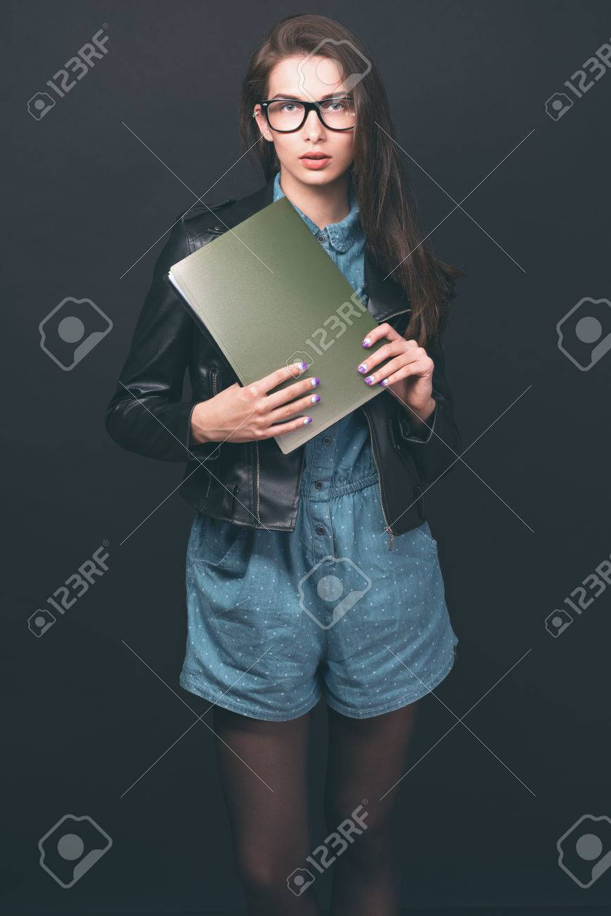 beautiful young girl. glasses, denim overalls, a black leather