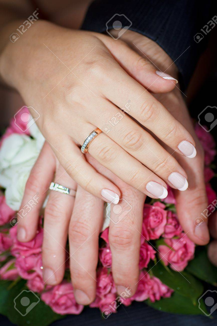 Hands Of Men And Women With Wedding Rings On Wedding Bouquet Stock ...