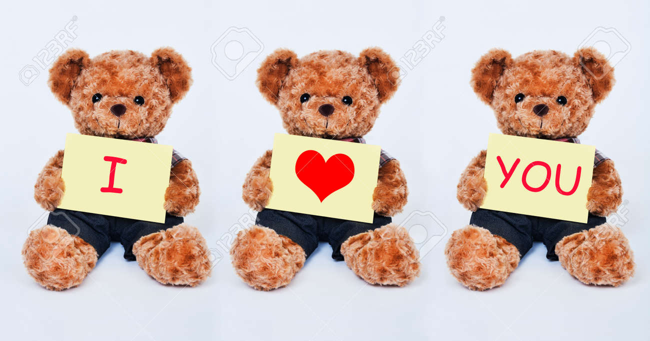 a cute teddy bear holding a yellow sign that says i love you.. stock