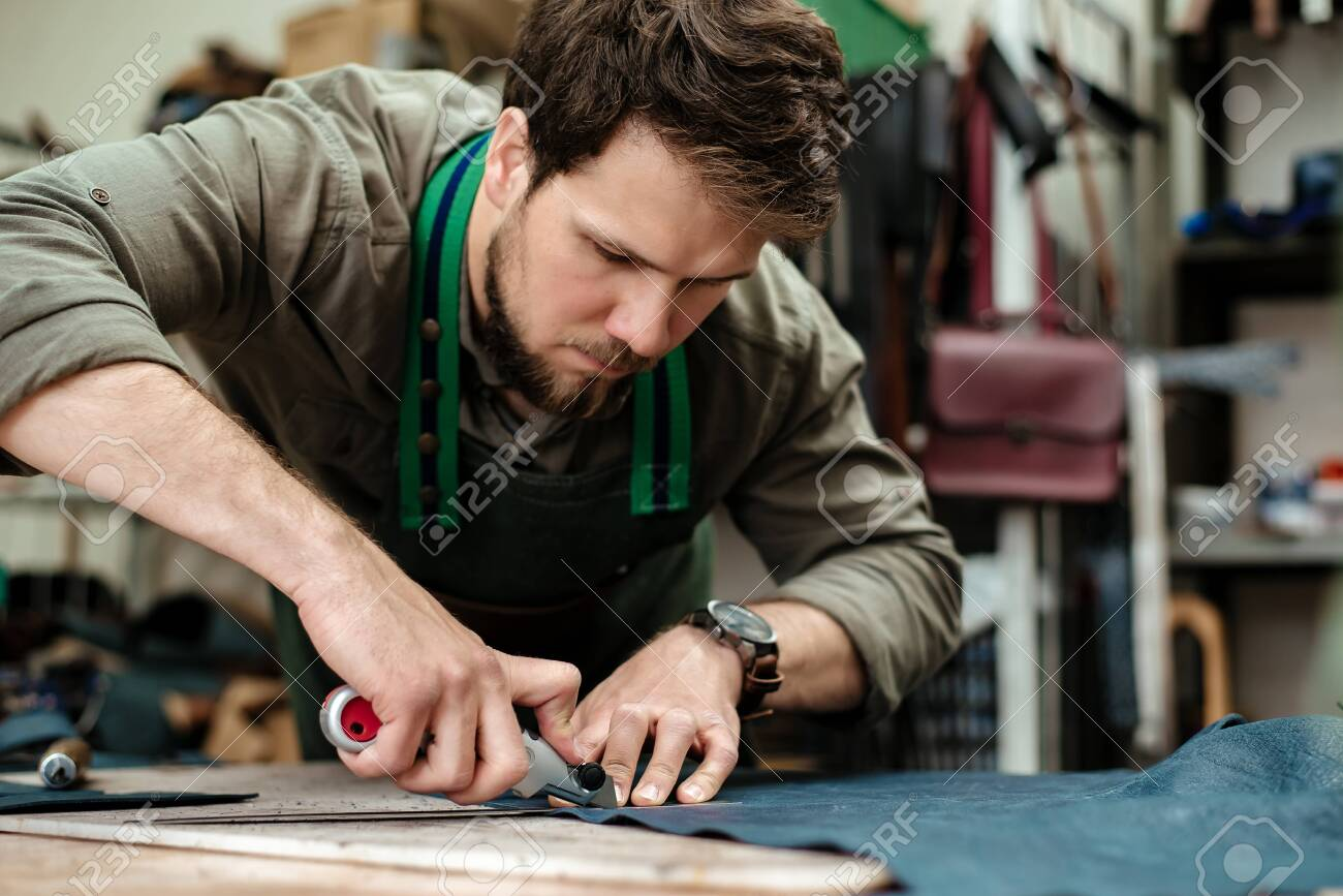 A master cuts natural leather for goods in his workshop - 120878582