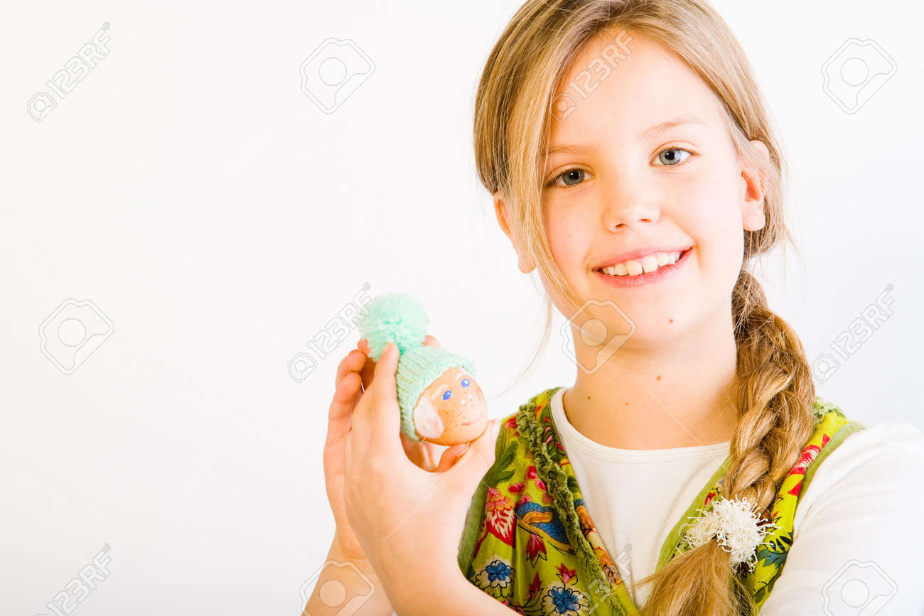 Studio portrait of a young blond girl who is showing her painted easter egg with a wool hat Stock Photo - 2369221