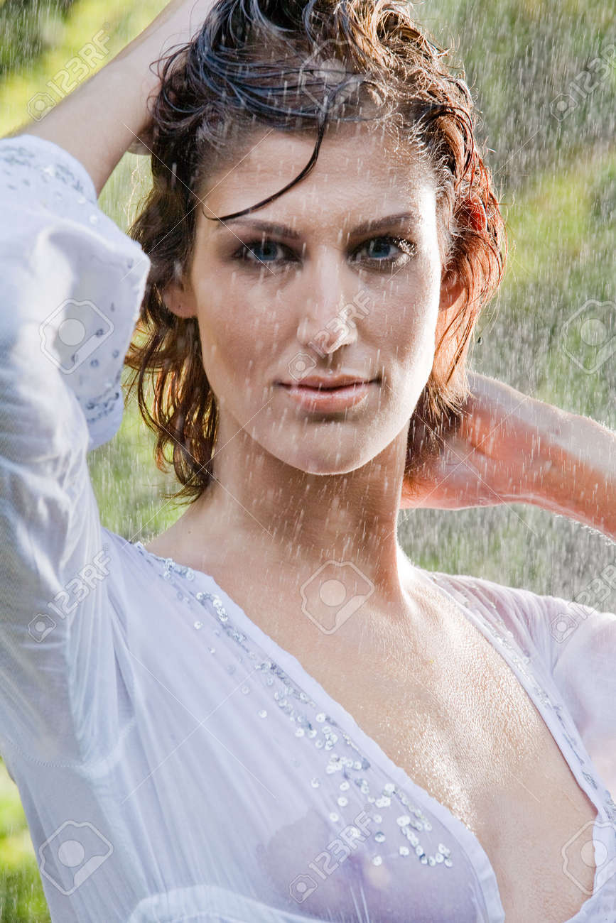 Brunette In See Through Blouse Standing In The Rain Stock Photo