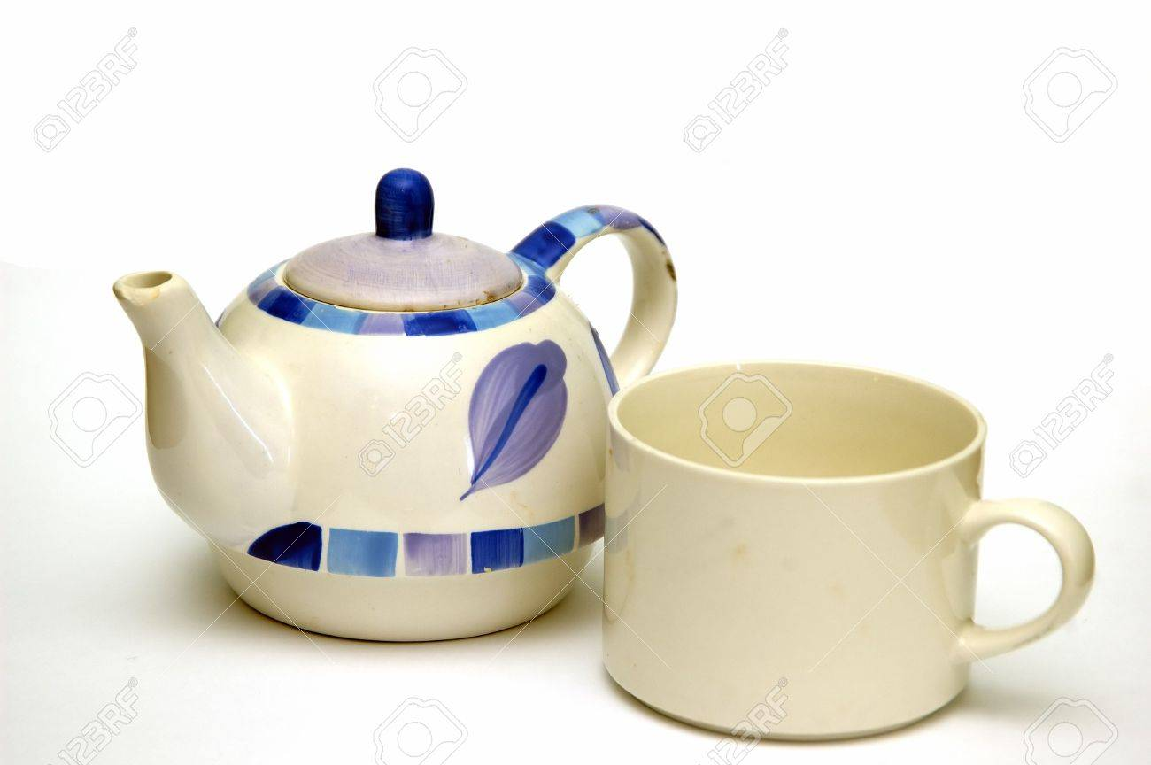 A Ceramic kettle and a tea cup  isolated against a white background Stock Photo - 765776