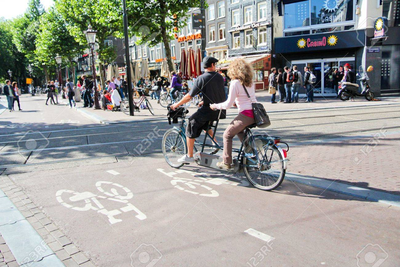 Couple riding tandem in a lane bike of Rembrandt place, Amsterdam  Stock Photo - 15877167