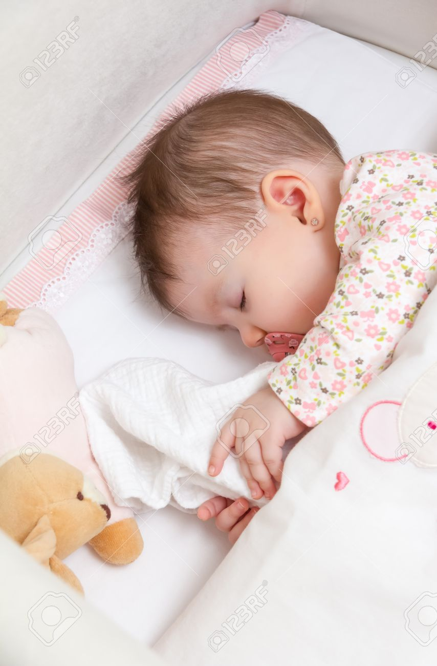 3da4e8137 Portrait of cute baby girl sleeping in a cot with pacifier and stuffed toy  Stock Photo
