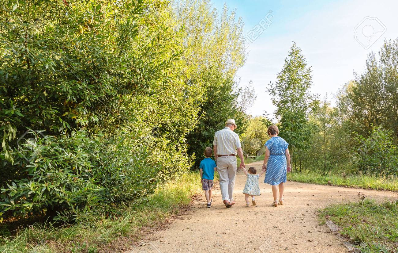 Back view of grandparents and grandchildren walking on a nature path Stock Photo - 31541182
