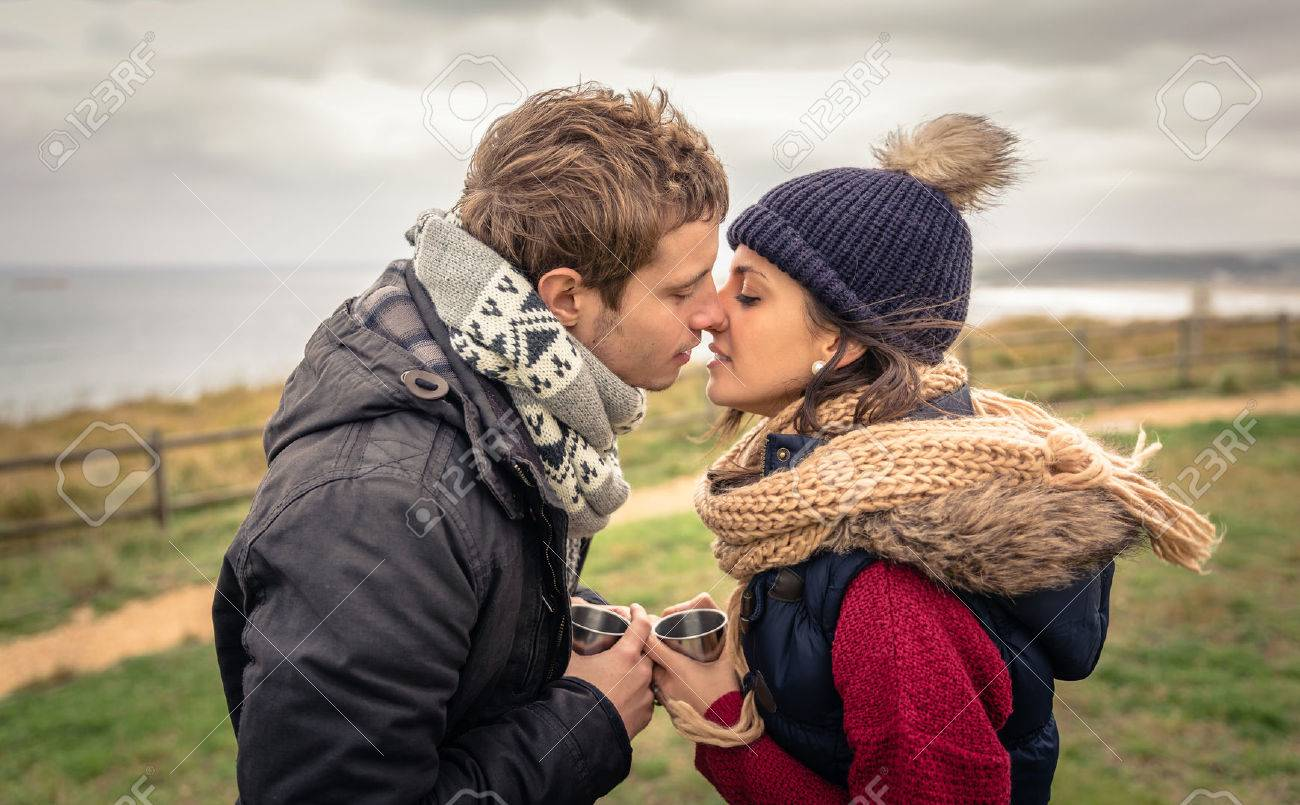 Portrait of young happy couple kissing and holding cups of hot beverage in a cold day with sea and dark cloudy sky on the background Stock Photo - 34523362