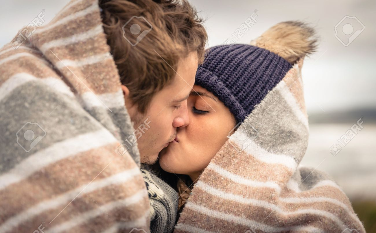 Closeup of young beautiful couple kissing under blanket in a cold day with sea and dark cloudy sky on the background Stock Photo - 34782505