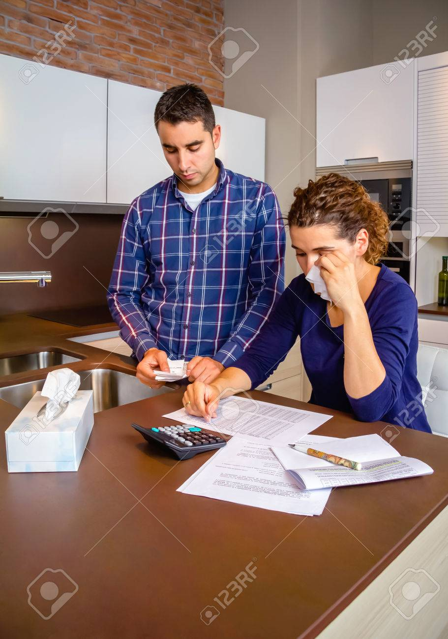 young unemployed husband reviewing the bills and his desperate stock photo young unemployed husband reviewing the bills and his desperate wife crying by their debts financial family problems concept