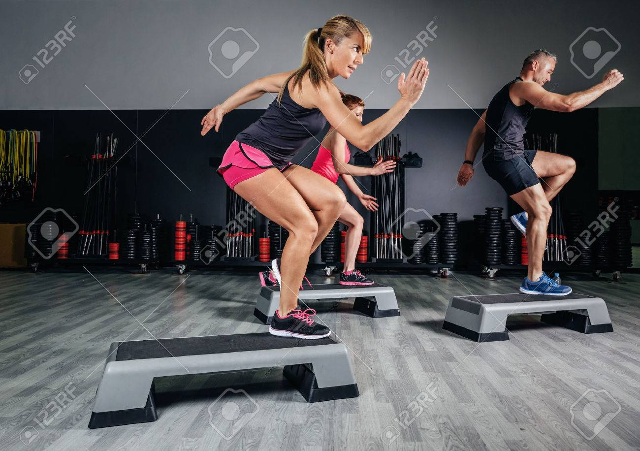 Athletic woman trainer doing aerobic class with steppers to people group on a fitness center. Sport and health concept. Stock Photo - 45884821
