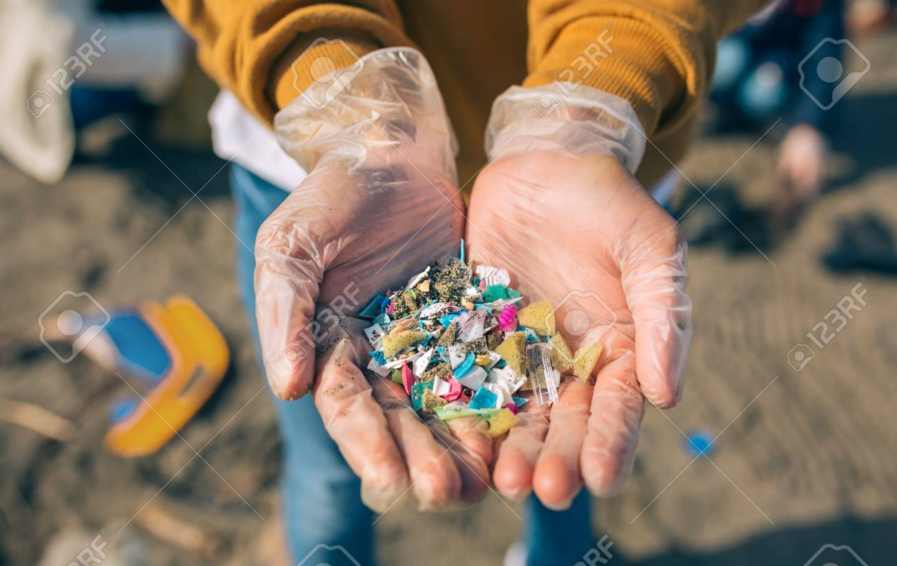 Detail of hands showing microplastics on the beach - 123928153