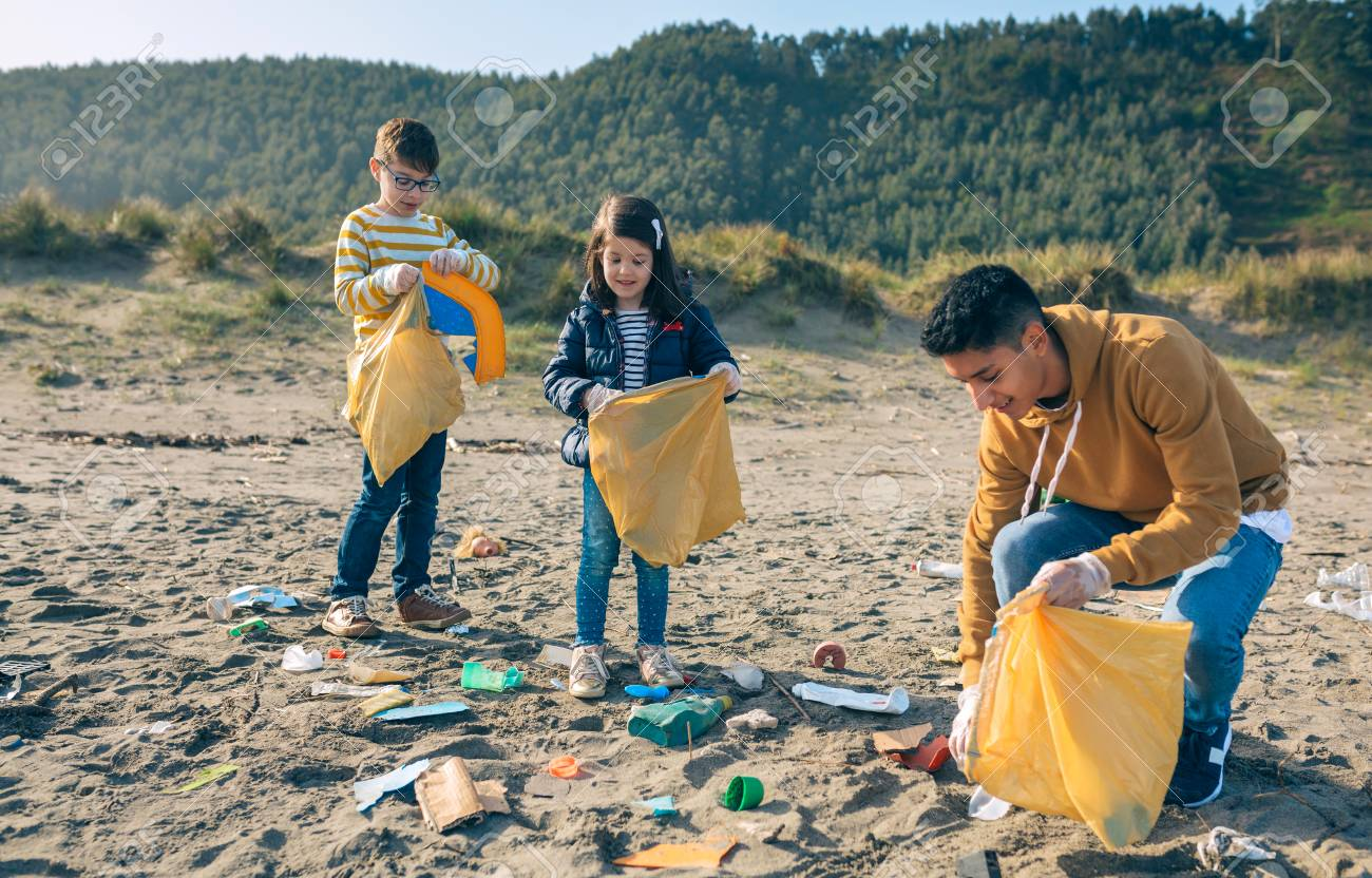 Group of young volunteers picking up trash on the beach - 123928218