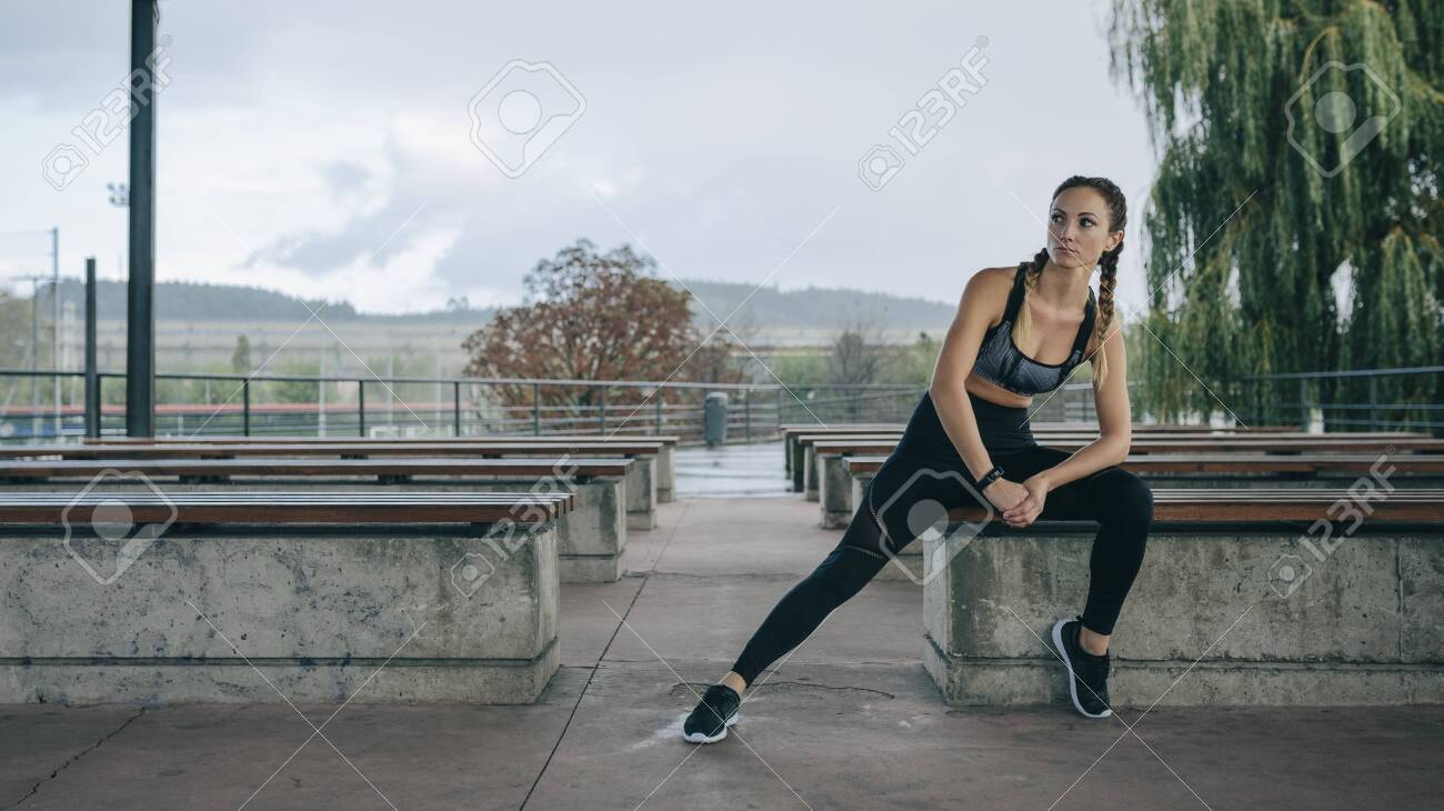 Young sportswoman posing sitting on a bench outdoors - 135303109
