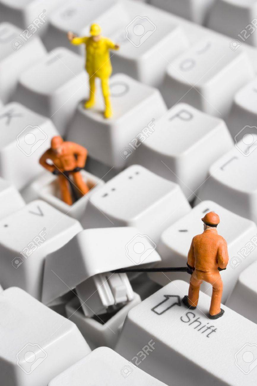 Worker figurines posed to look as though they are working on a computer keyboard. Stock Photo - 7342099