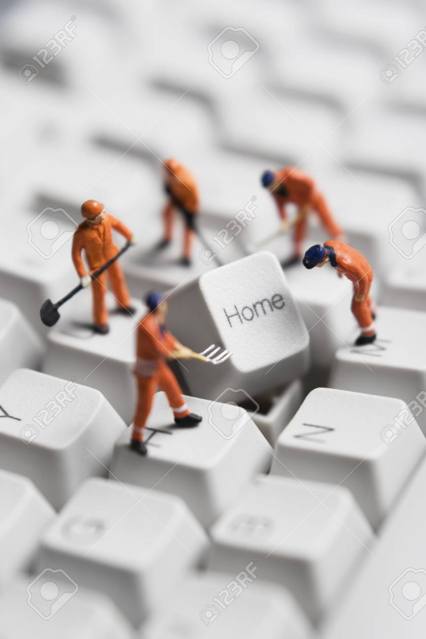 Worker figurines posed around the Home key on a computer keyboard. Stock Photo - 7652919