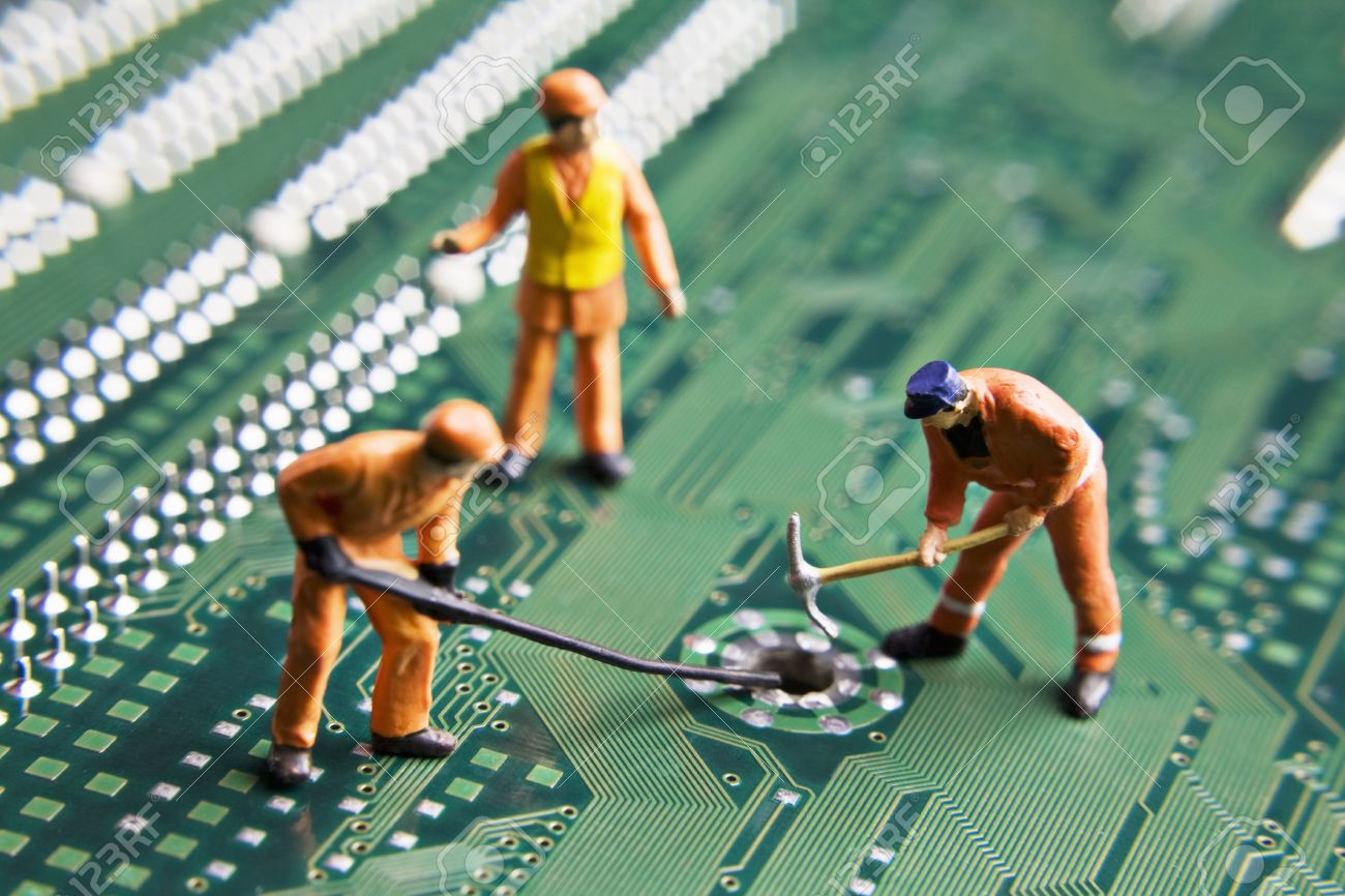 Worker figurines placed on a computer circuit board Stock Photo - 7903251