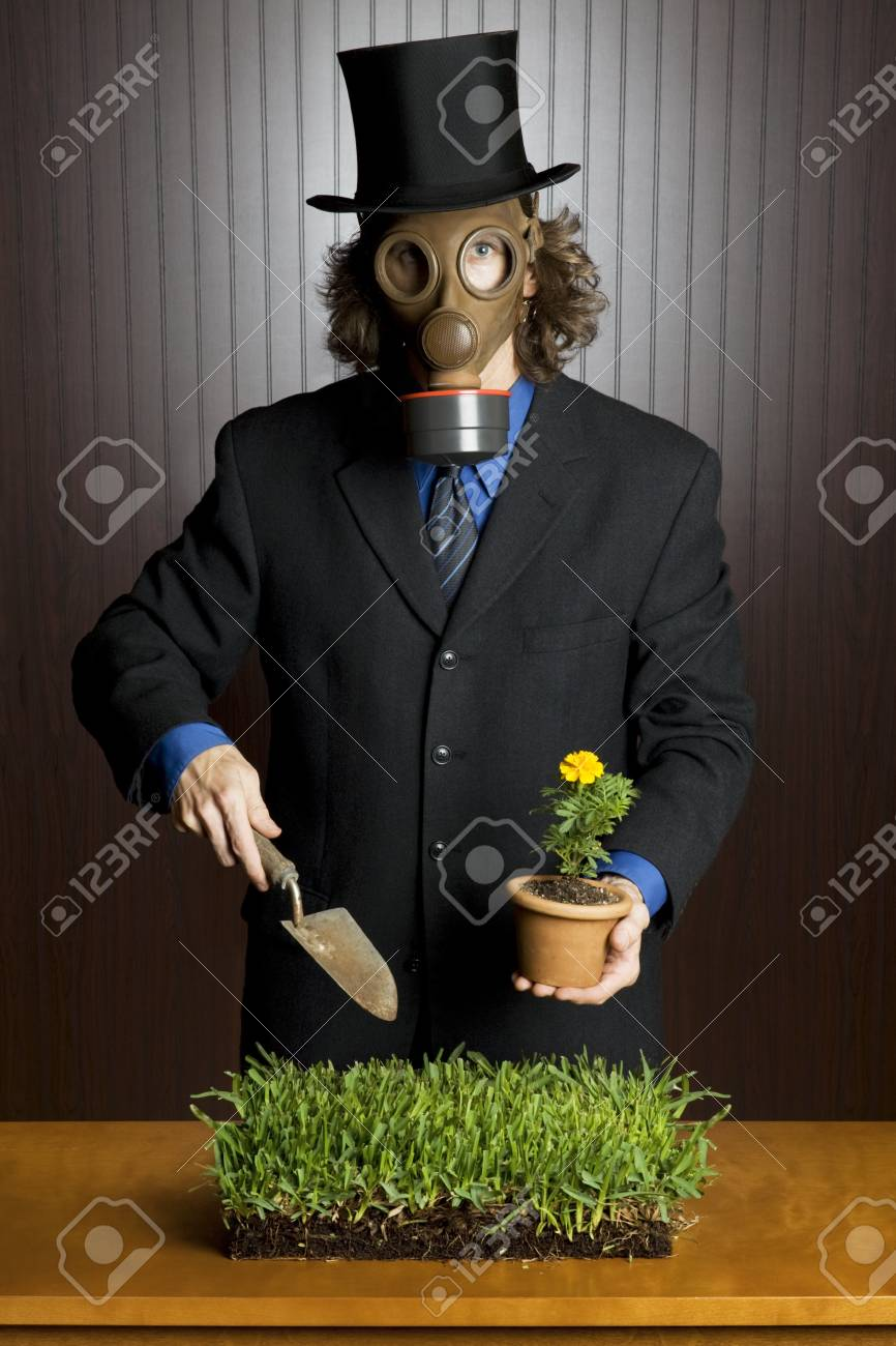 Businessman wearing a gasmask holding a potting shovel standing over a patch of grass Stock Photo - 8778028
