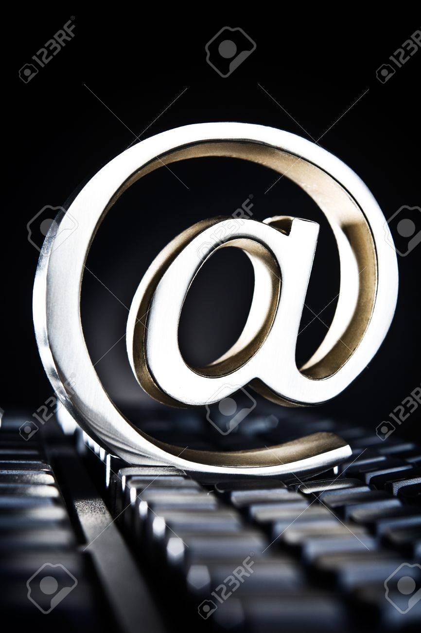 At sign, at symbol, paperweight placed on computer keyboard