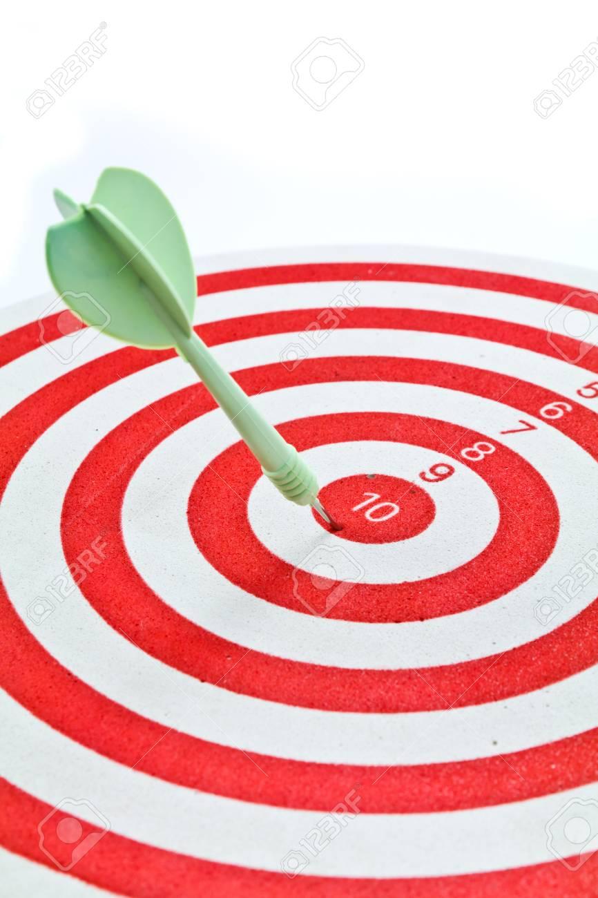 Green dart on red dart board Stock Photo - 10441377