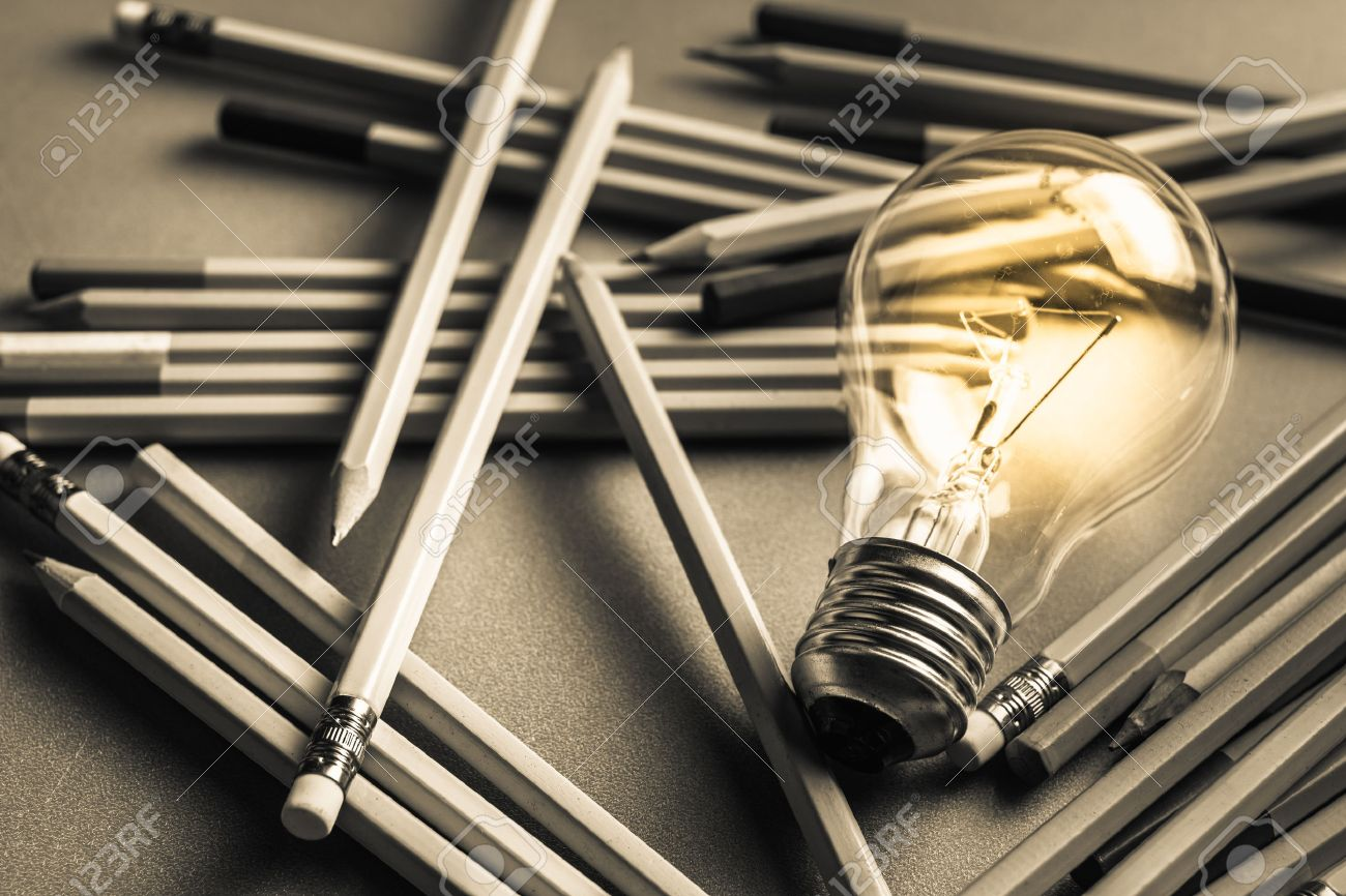 creative writing, light bulb and many pencils on the table stock
